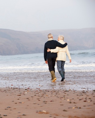 Senior Couple Walking Along Winter Beach